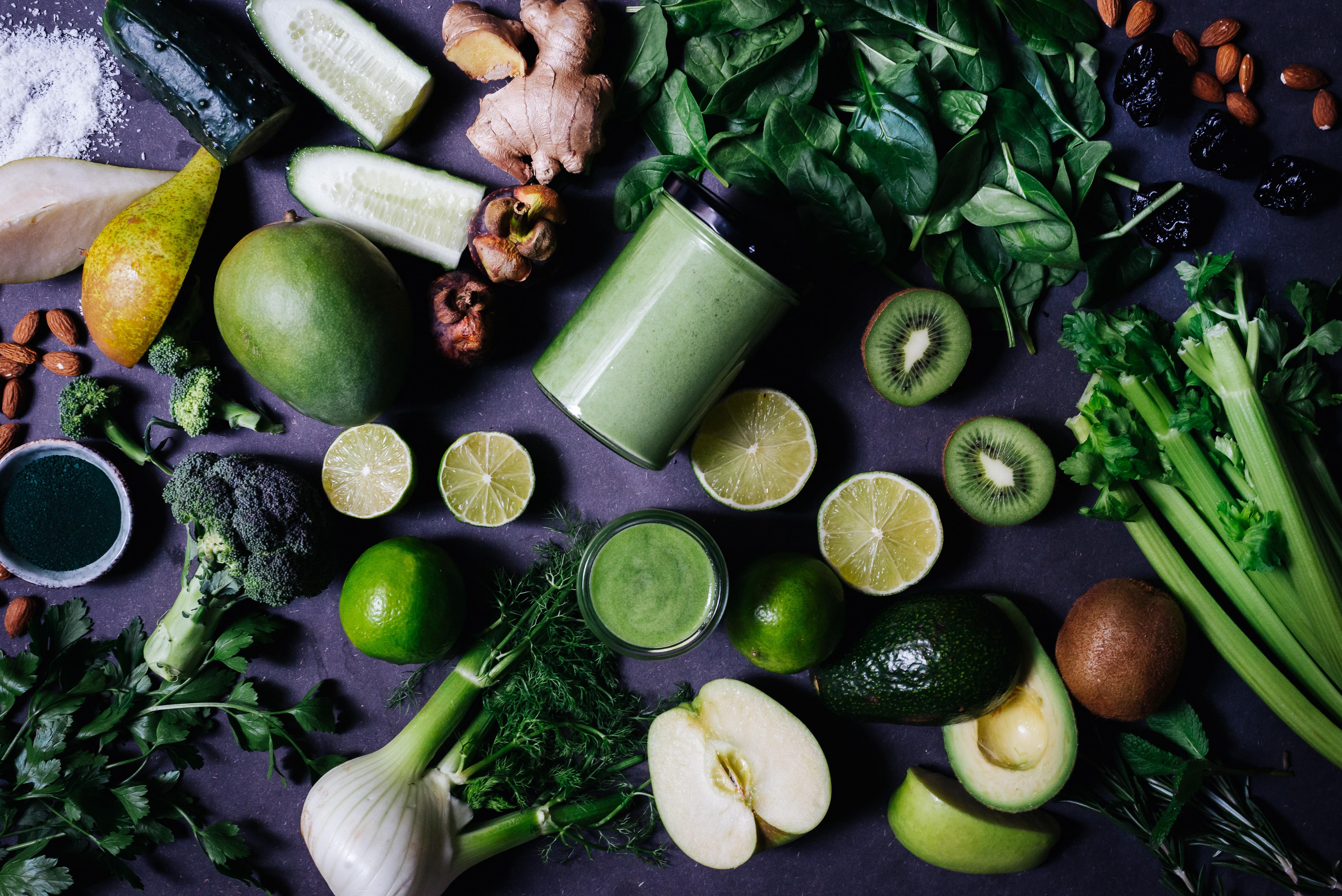 Grüner Smoothie im Glas umgeben von grünem Obst und Gemüse